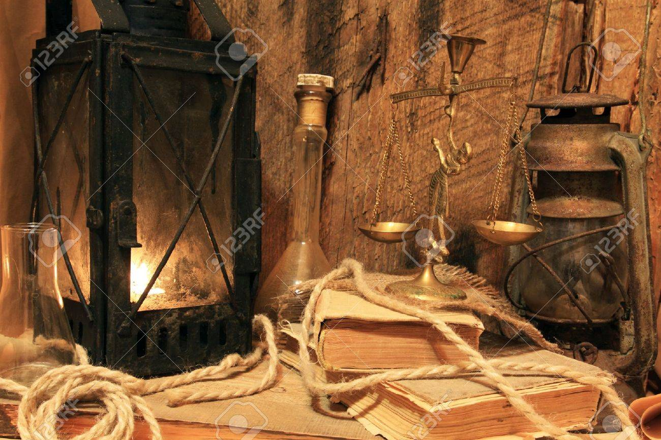Still life - old lamps, books and balance on wooden background Stock Photo - 10015737