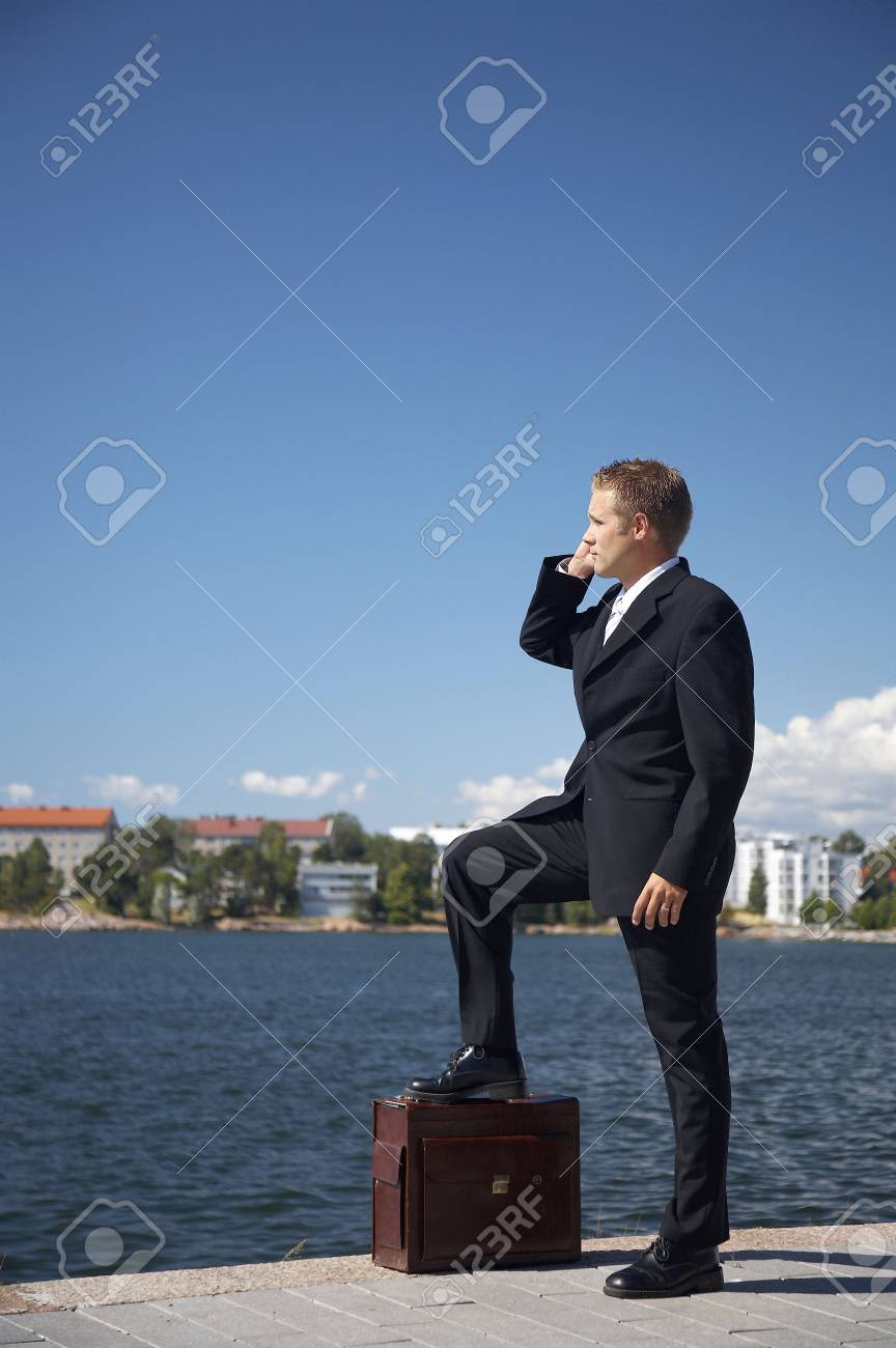 Businessman talking on the mobile outdoors with one leg on the briefcase Stock Photo - 3193436