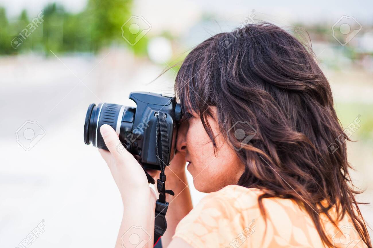 A young girl taking photograph with reflex camera - 147979670