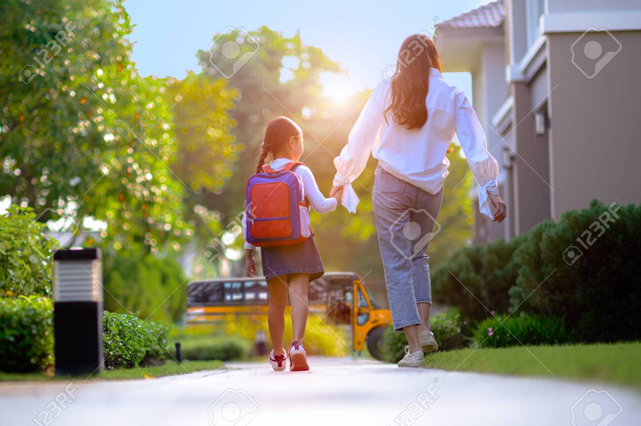 mother on the way sending daughter girl to school bus in the first day of study learning - 133881349