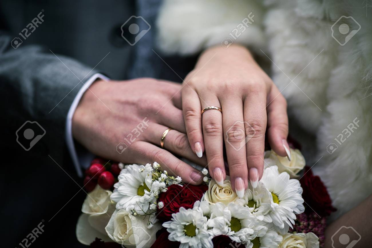 Bride And Groom Next To Wedding Rings On Their Hands, Male And ...