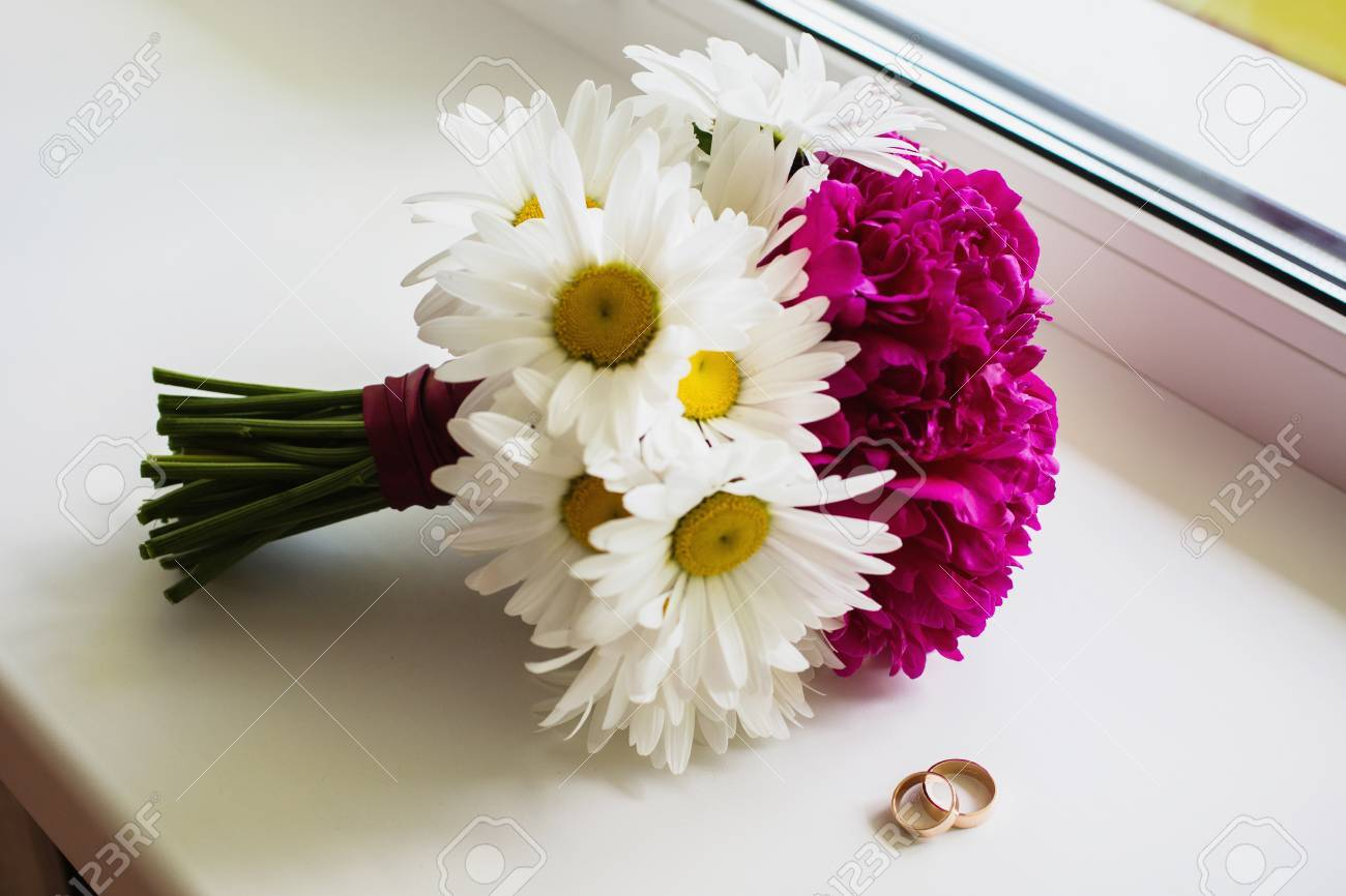 Wedding bouquet of white and purple flowers lay on the window stock photo wedding bouquet of white and purple flowers lay on the window morning of the bride the grooms fees rings lie on the windowsill izmirmasajfo
