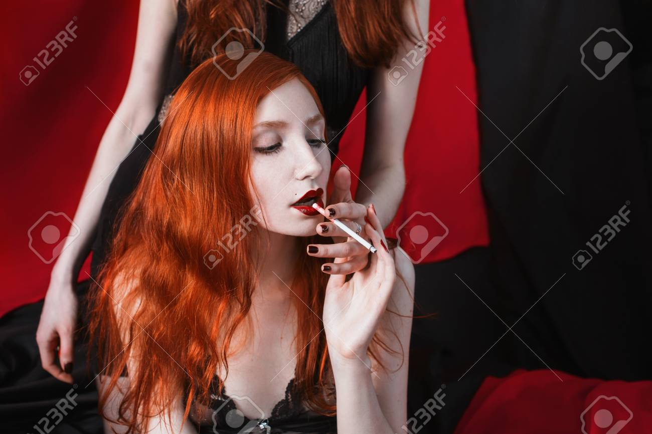 Stock Photo - Two red-haired girl hugging and smoke on black and red  background. Two lesbian women. Long red hair. Beautiful sexy lingerie  transparent.