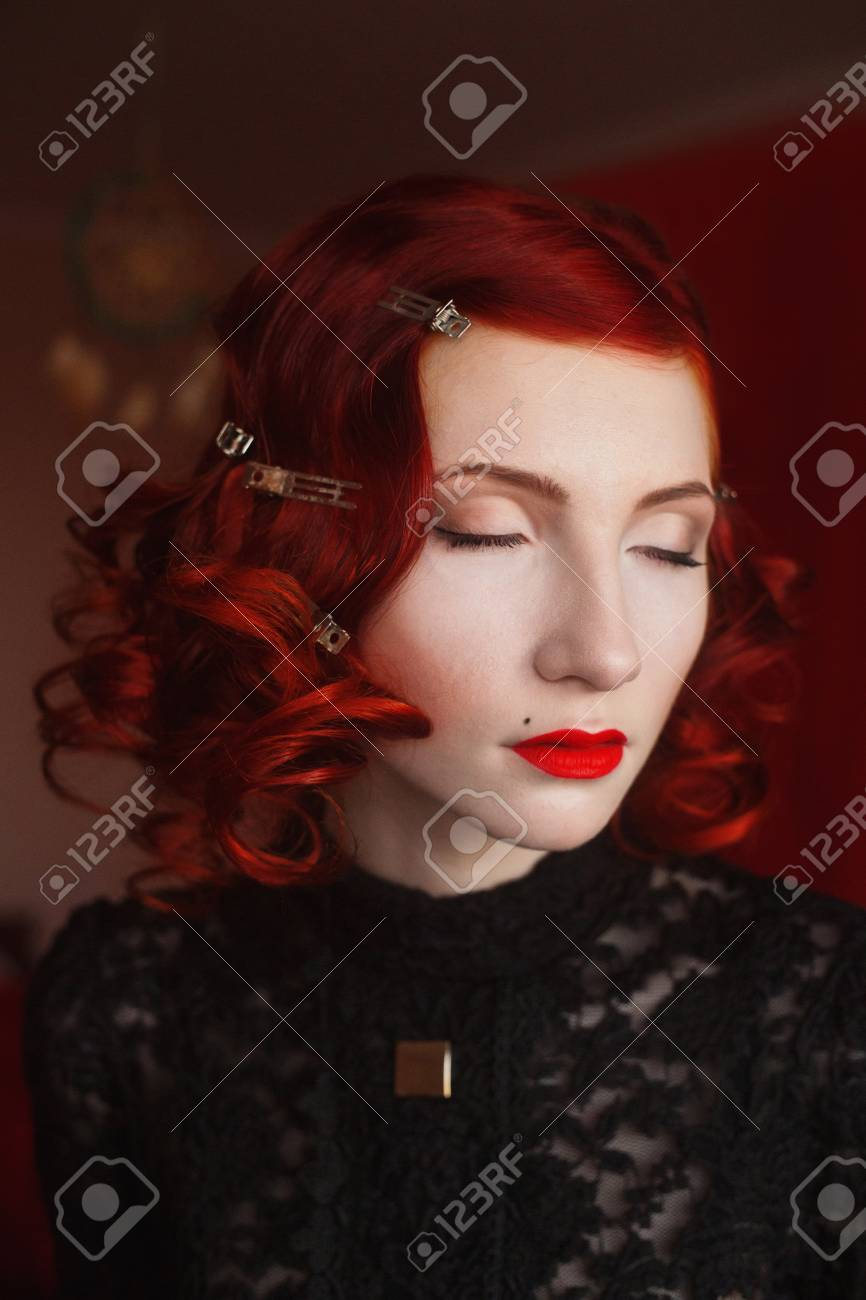 A Woman With Red Curly Hair In A Black Dress And Retro Makeup