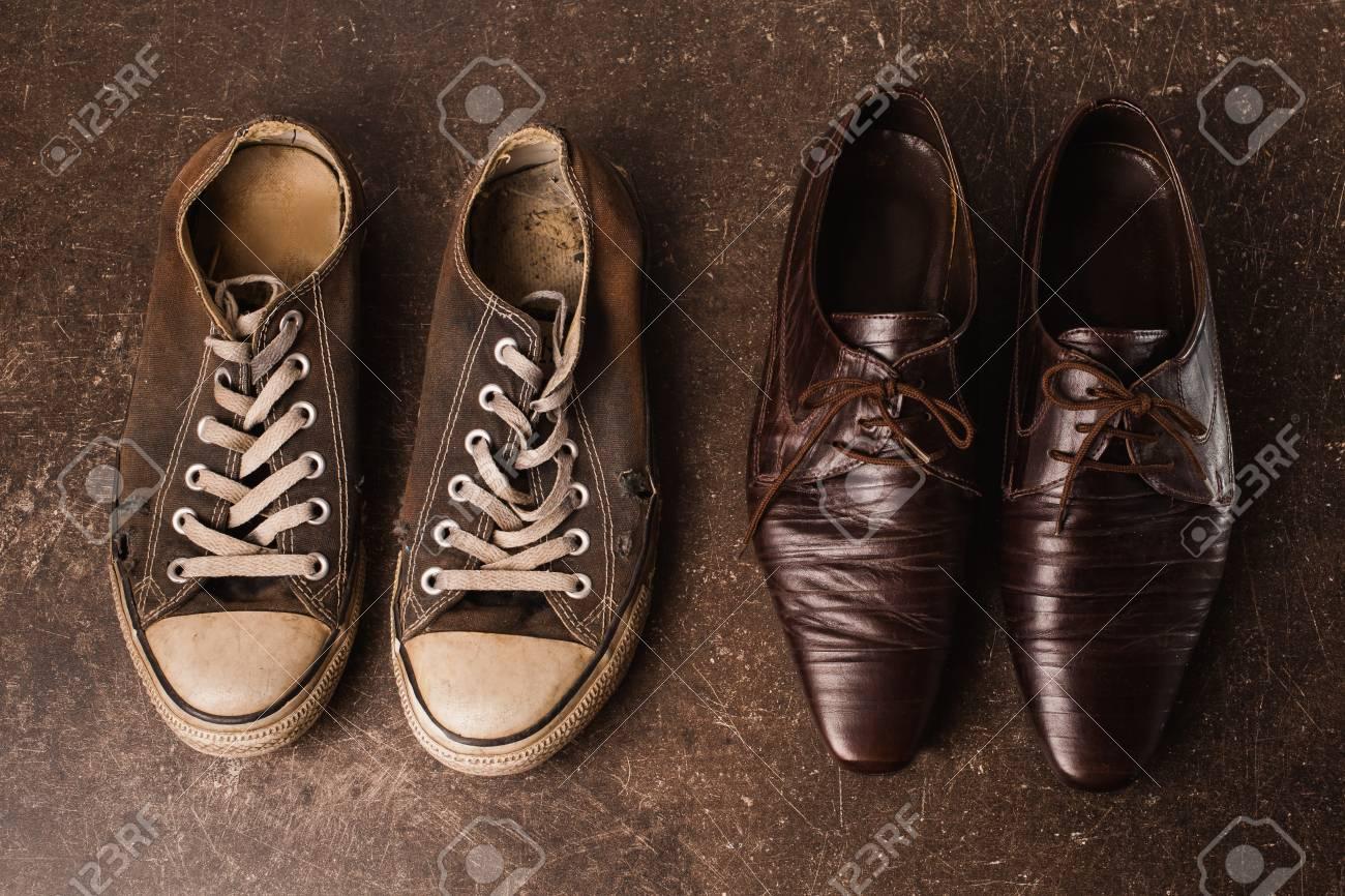 c5d04e477d3383 Alte schwarze Turnschuhe und braune klassische Schuhe auf einem dunklen  Marmorhintergrund. Schuhe für Outdoor-