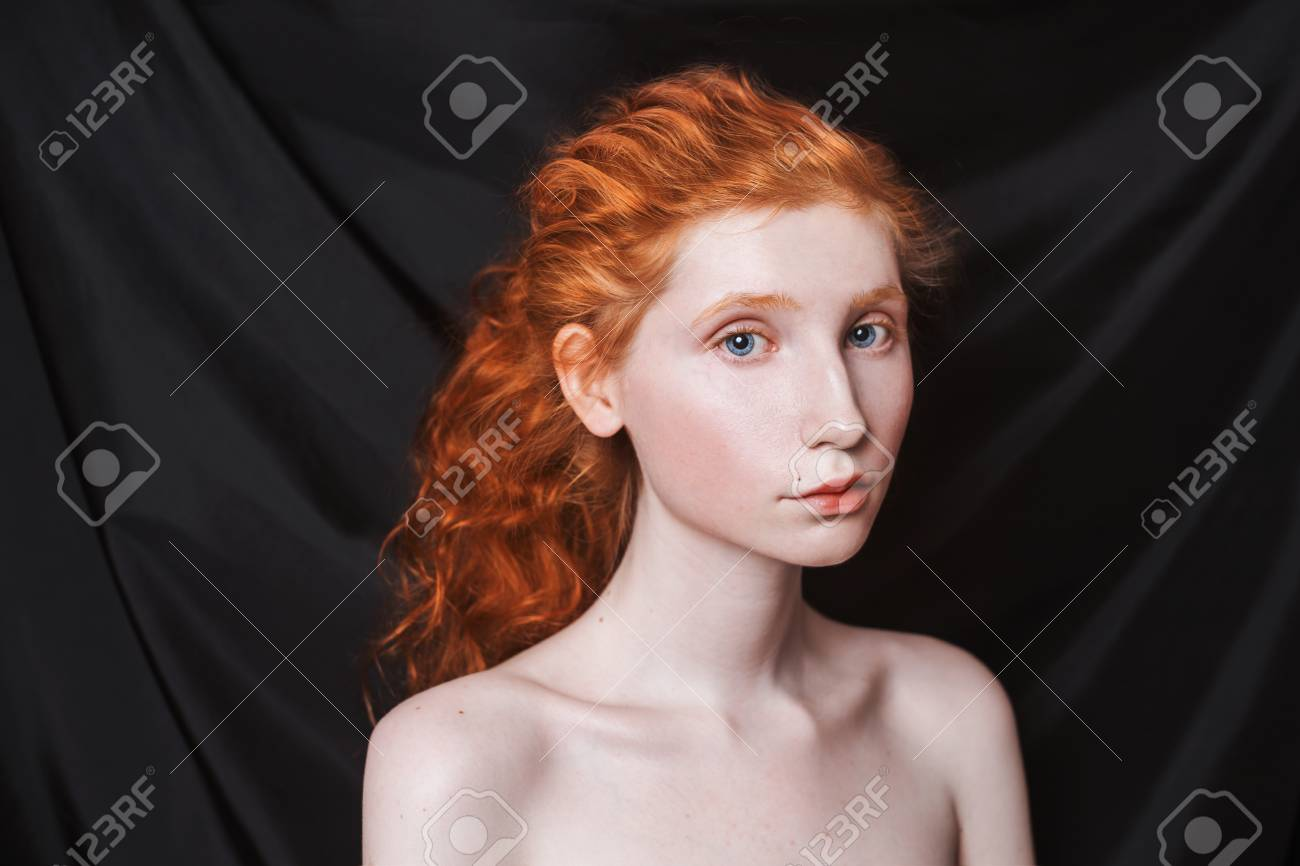 Woman With Long Curly Red Hair Gathered In Ponytail On Black