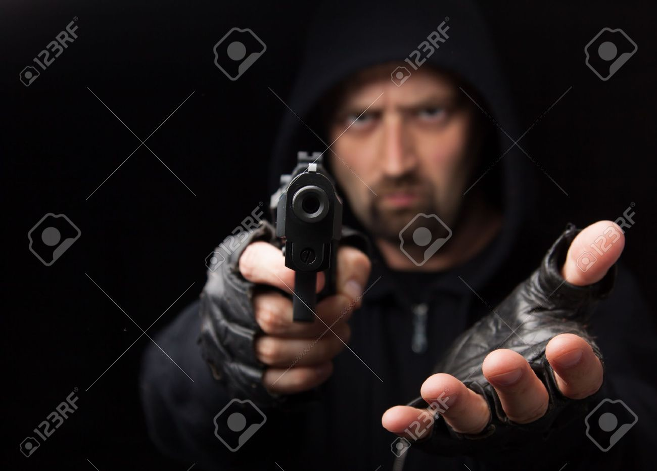 Robber with gun holding out hand against a black background - 14624263