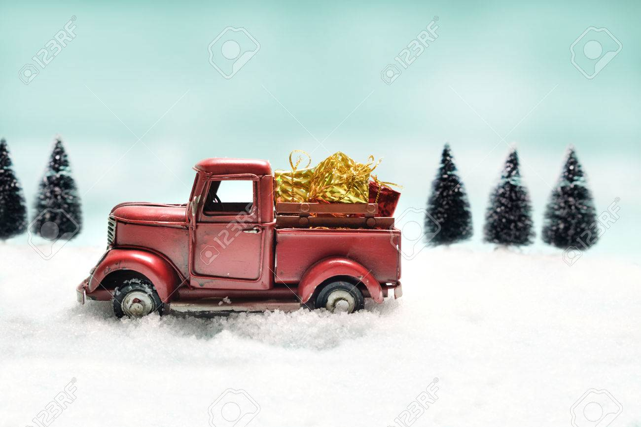 68993272 red truck toy carrying a christmas gift on sweet pastel retro turquoise color background