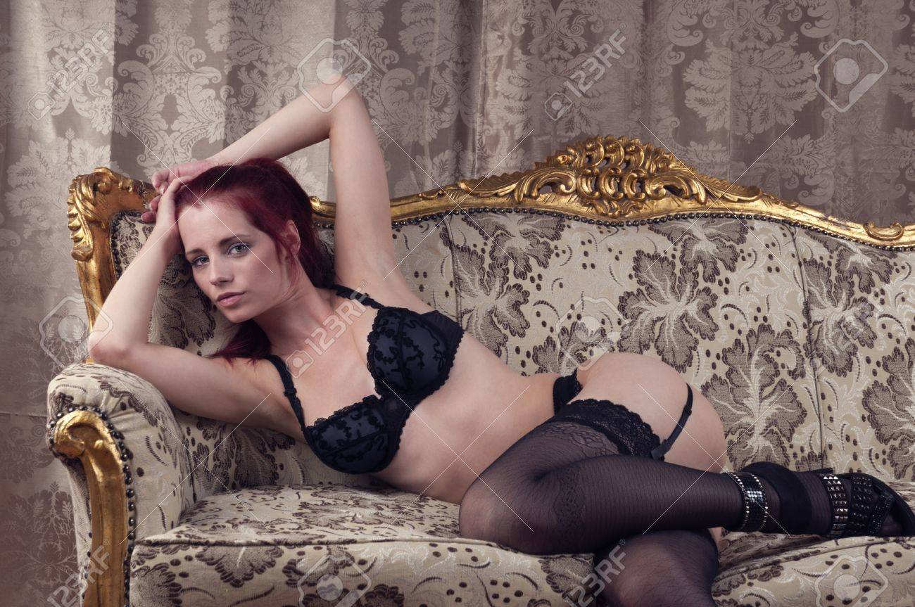 beautiful redhead wearing lingerie and high heels on a couch Stock Photo - 10276092