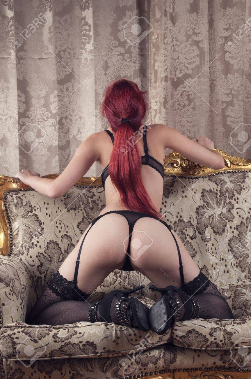 beautiful redhead wearing lingerie and high heels on a couch Stock Photo - 10276286