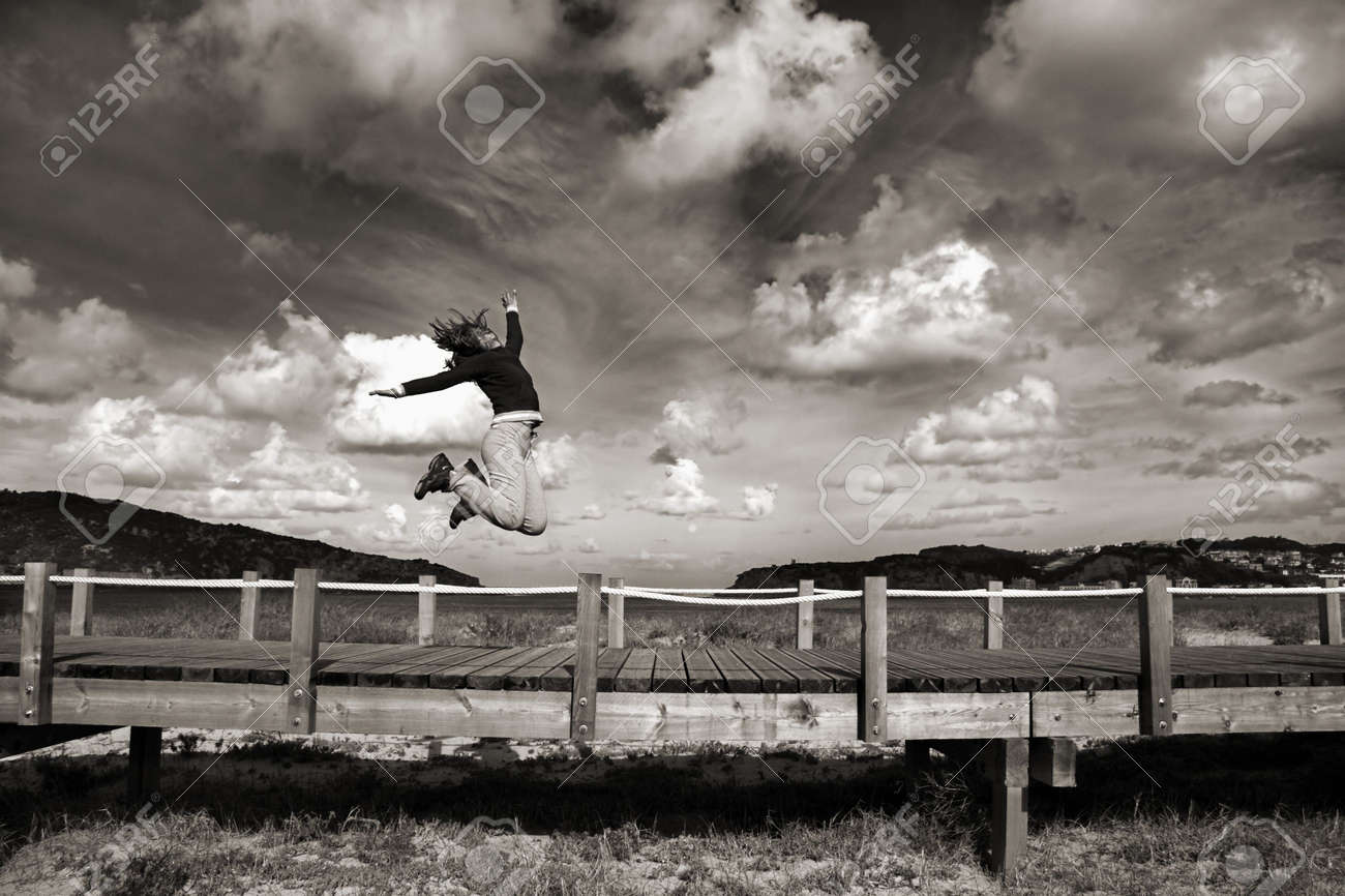 Young woman jumping for fun in a beautiful day (Black and white version) Stock Photo - 1207256