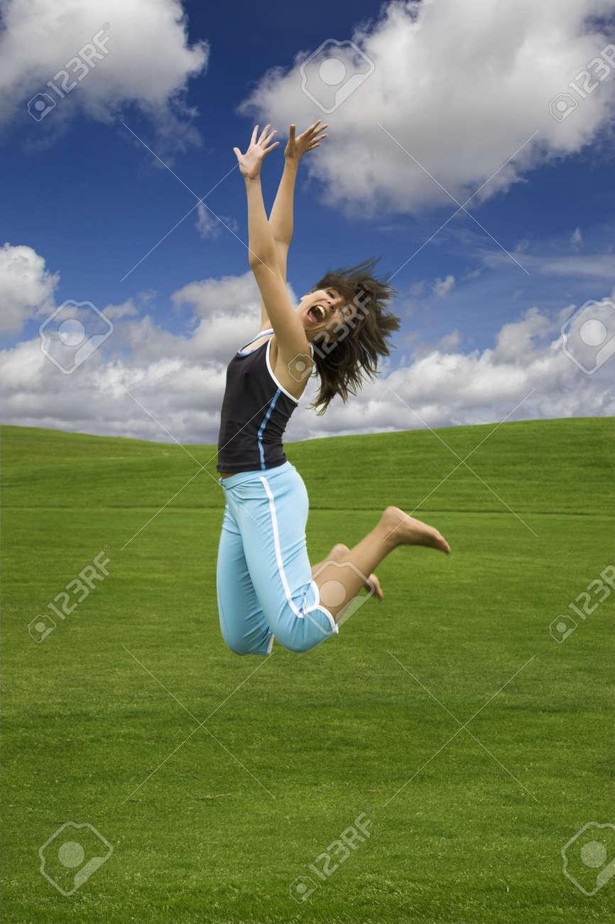 Beautiful happy woman jumping on a green field Stock Photo - 1320504