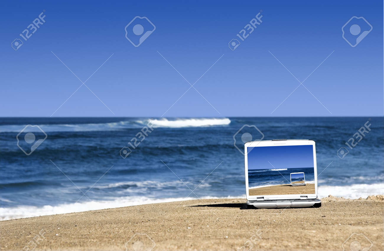 Open laptop on a beautiful beach with a great blue sky Stock Photo - 2953934