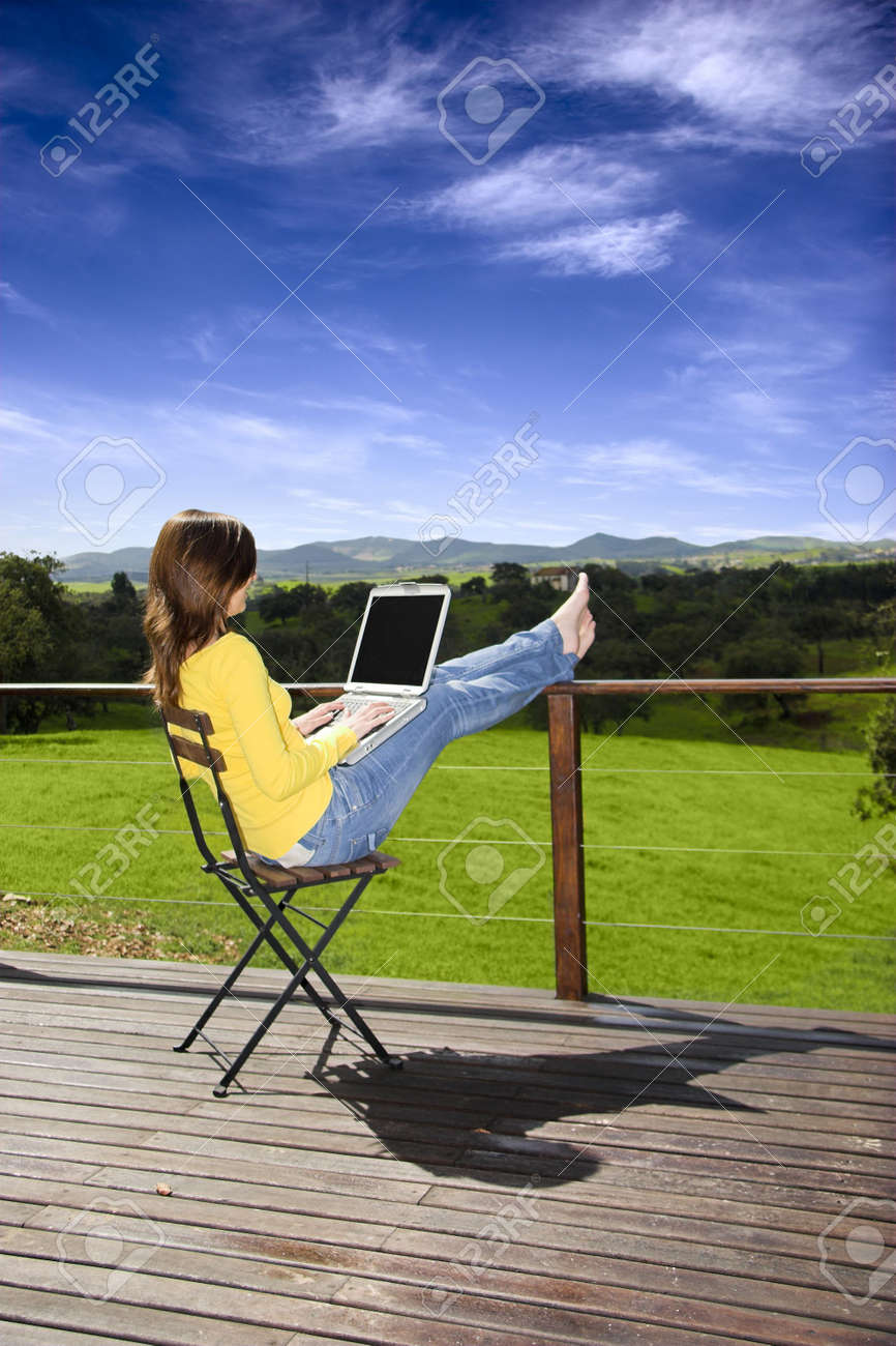 Woman enjoying a beautiful day with a laptop on her home-field Stock Photo - 3072352