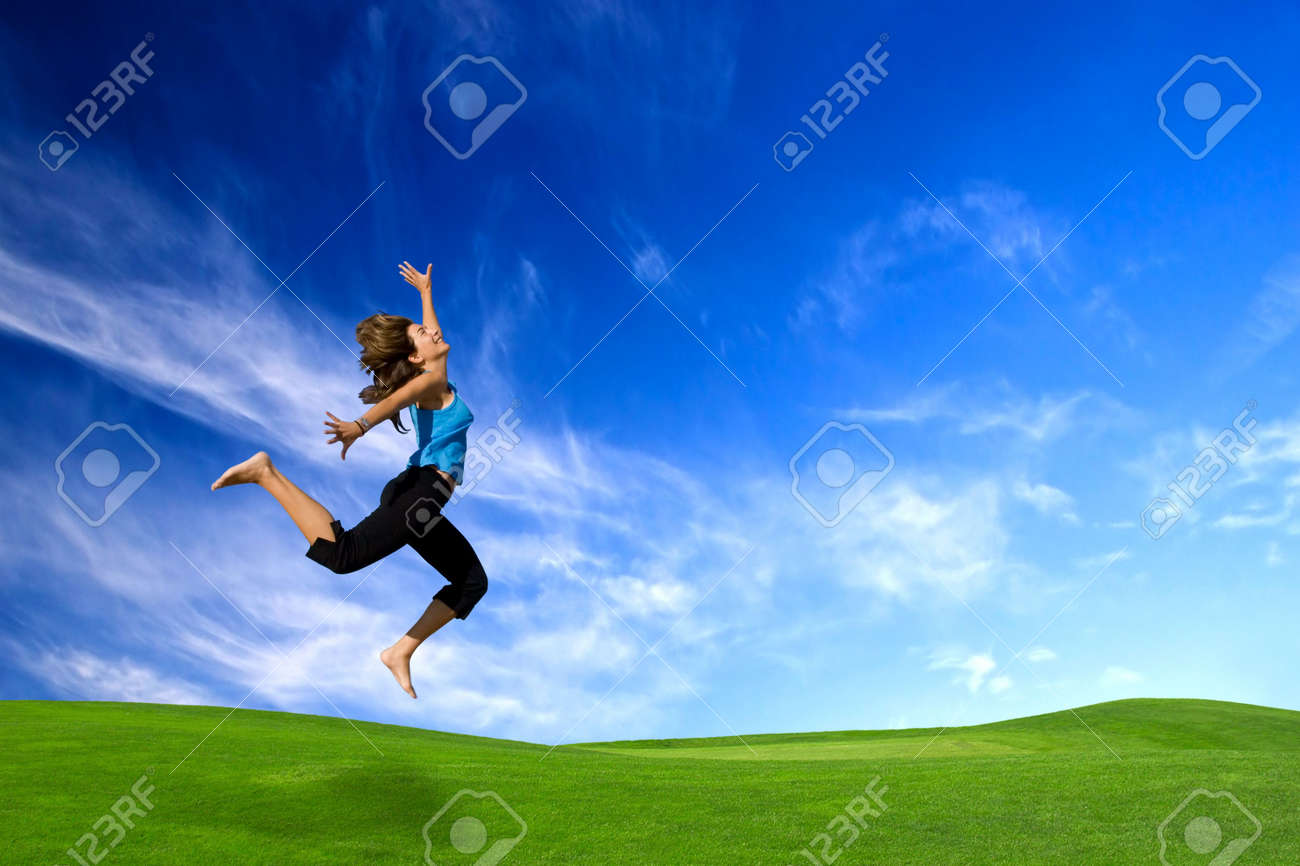 Beautiful athletic woman jumping on a green meadow Stock Photo - 4851380