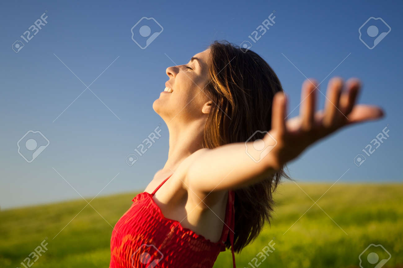 Portrait of beautiful young woman relaxing on the field with both arms open Stock Photo - 5067543