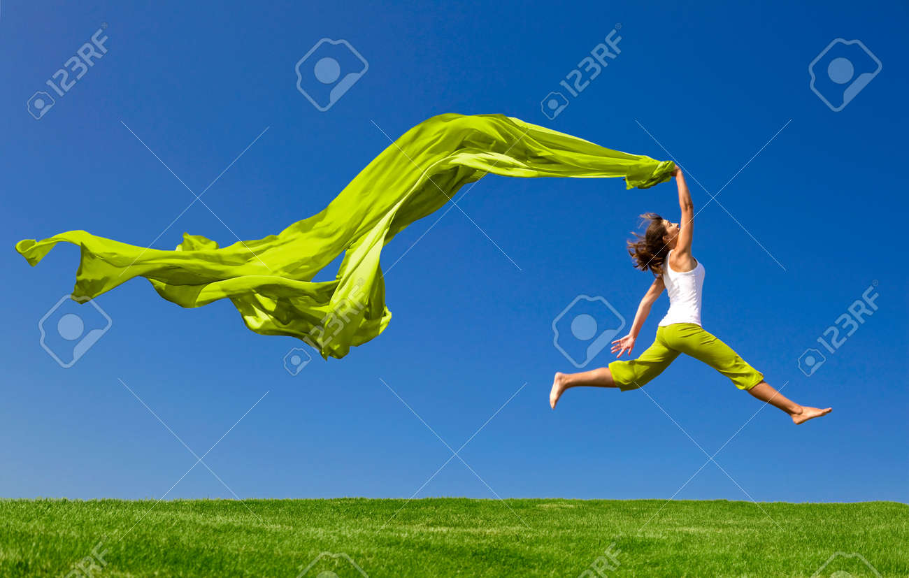 Beautiful young woman jumping on  a green meadow with a colored tissue Stock Photo - 6534247