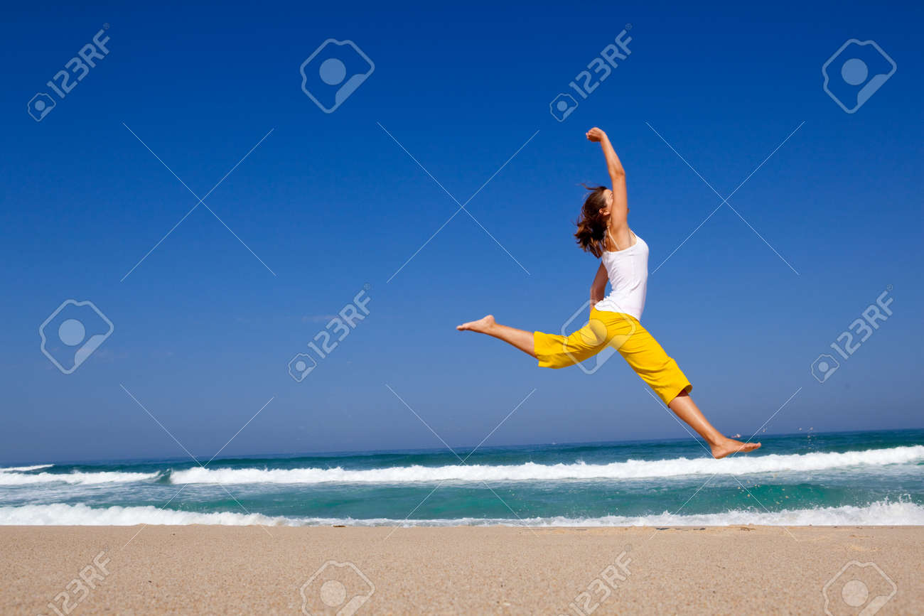 Beautiful young woman jumping on the beach - 6631362