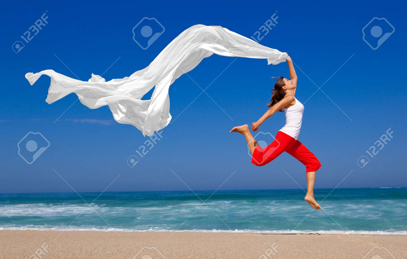 Beautiful young woman jumping on  the beach with a colored tissue Stock Photo - 8086373