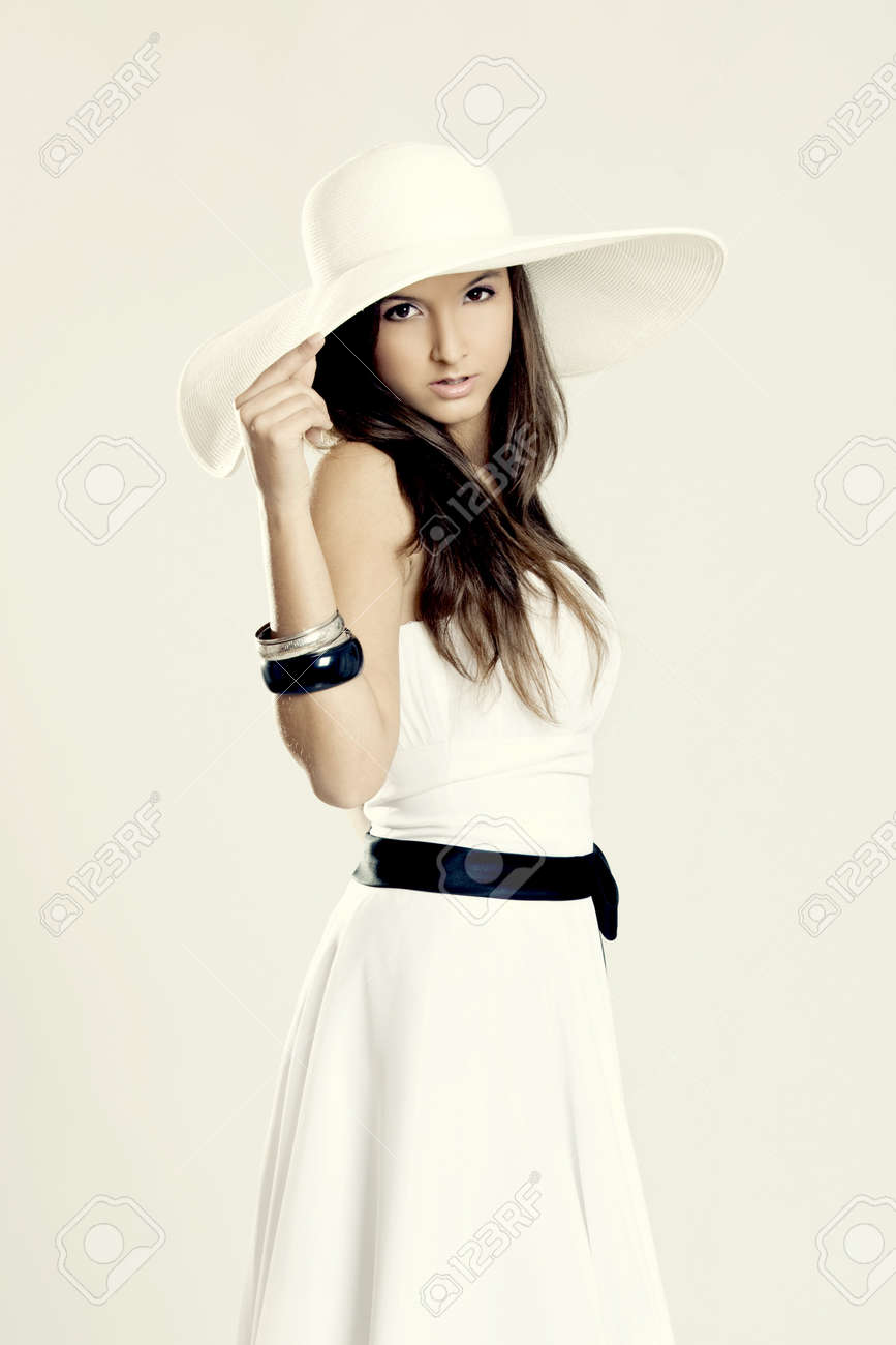 Beautiful and fashion young woman posing and wearing a wonderful white dress with a white hat Stock Photo - 9832975