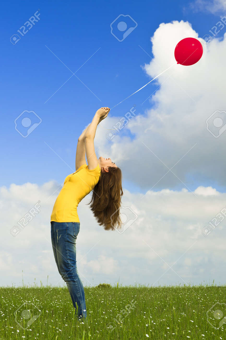 Happy young woman holding a red balloon on a green meadow Stock Photo - 10017636