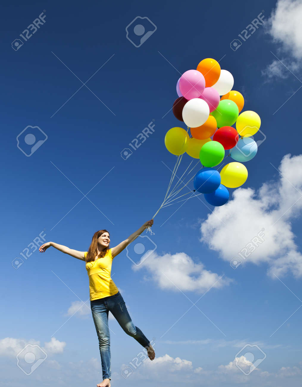 Happy young woman holding colorful balloons and flying over a green meadow Stock Photo - 10017635