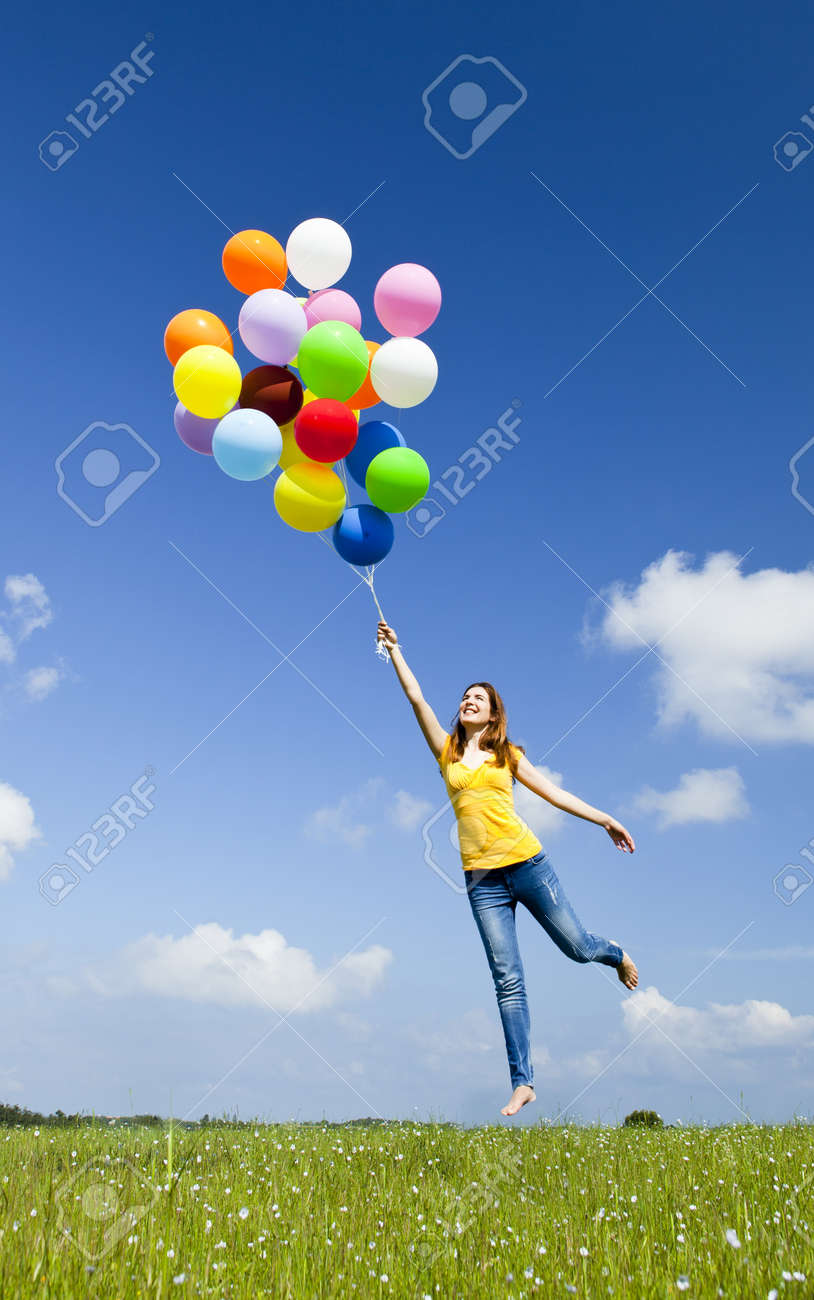 Happy young woman holding colorful balloons and flying over a green meadow - 10017637