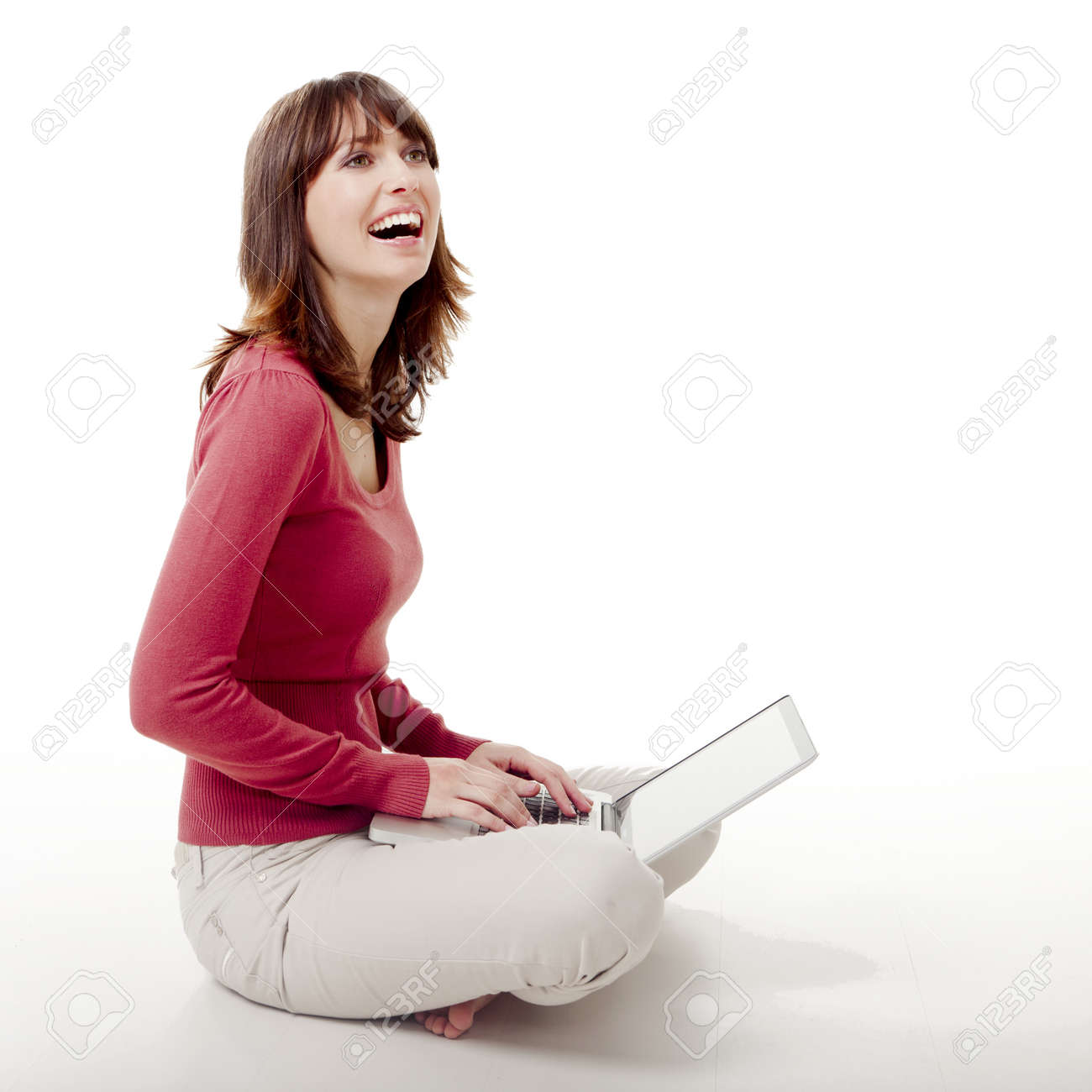Beautiful woman sitting on the floor laughing  and working with a laptop Stock Photo - 12165271