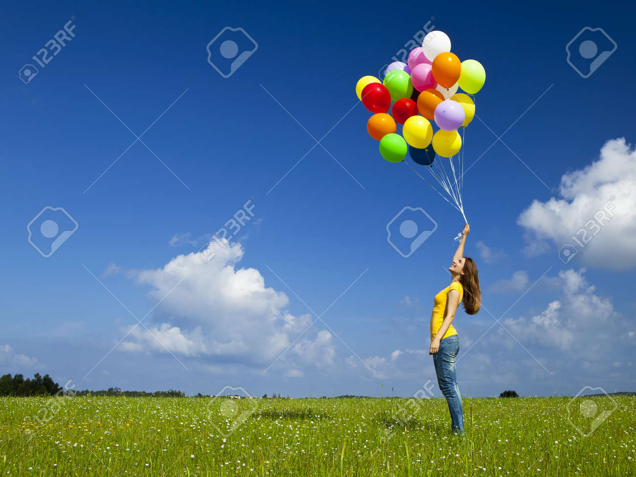 Happy young woman with colorful balloons on a green meadow Stock Photo - 12165409