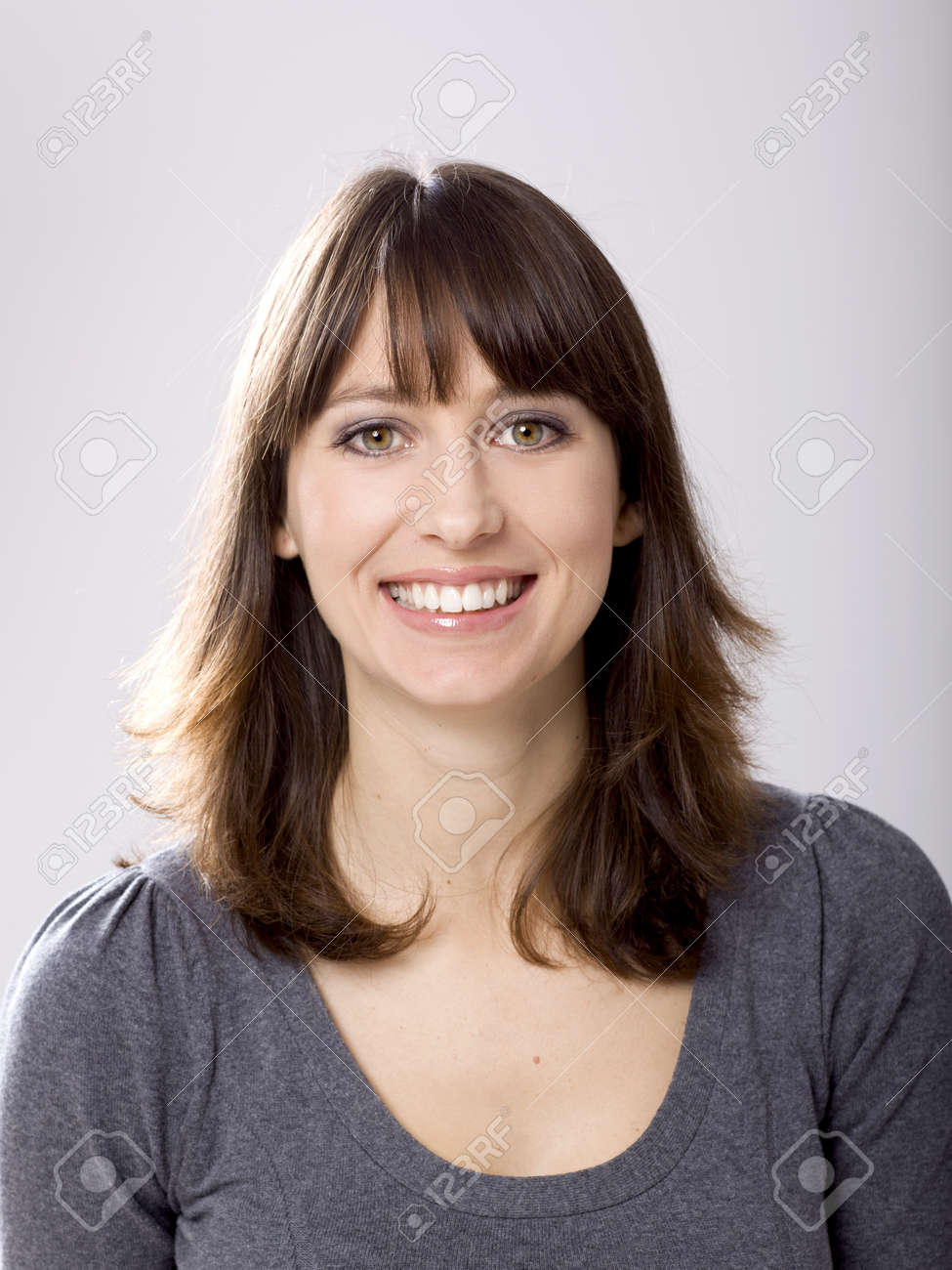 Beautiful young woman smiling, against a gray background Stock Photo - 12670041