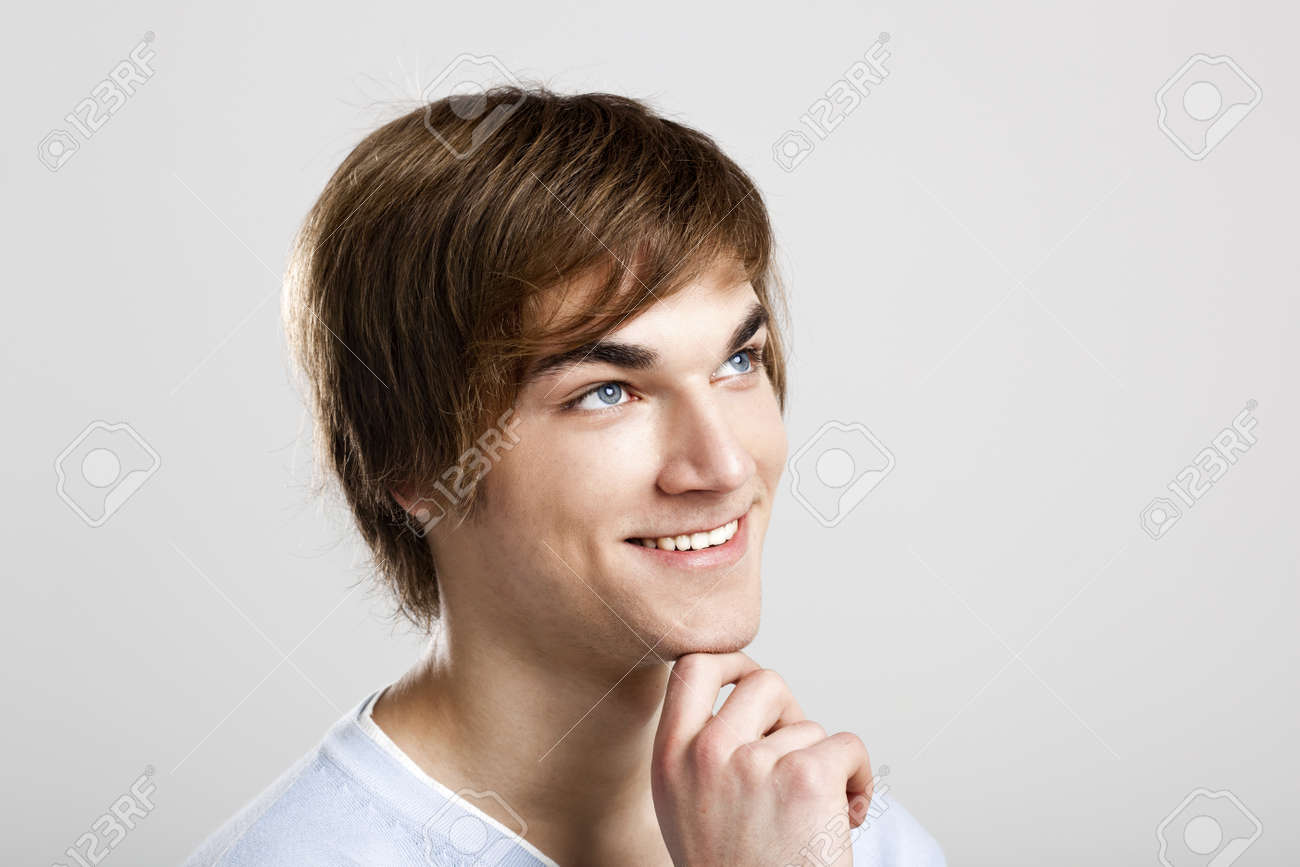 Portrait of a handsome and happy young man thinking, over a gray background Stock Photo - 12670106