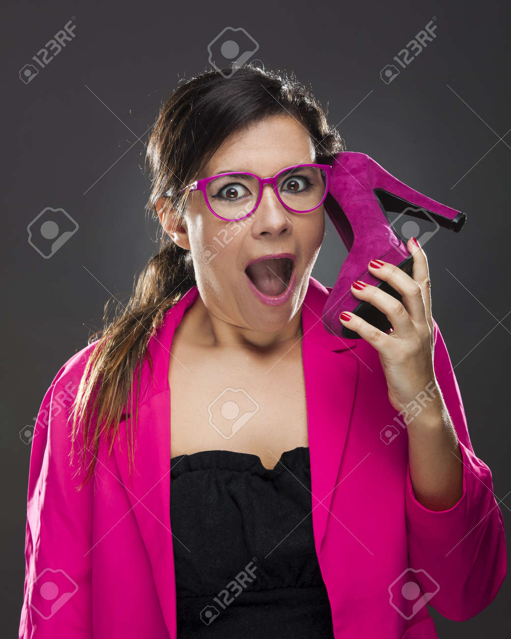Middle aged woman holding a shoe pretending it's a cell phone Stock Photo - 17041455