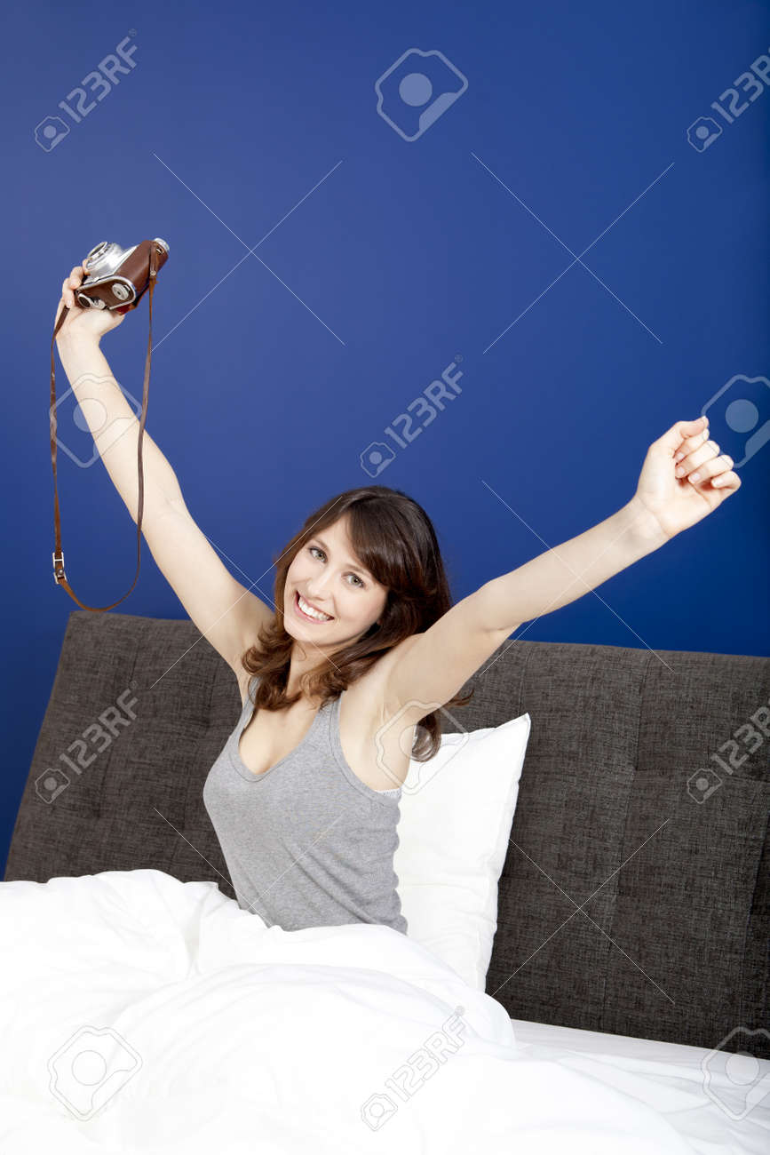 Young girl on the bed holding a photographic camara Stock Photo - 17241102