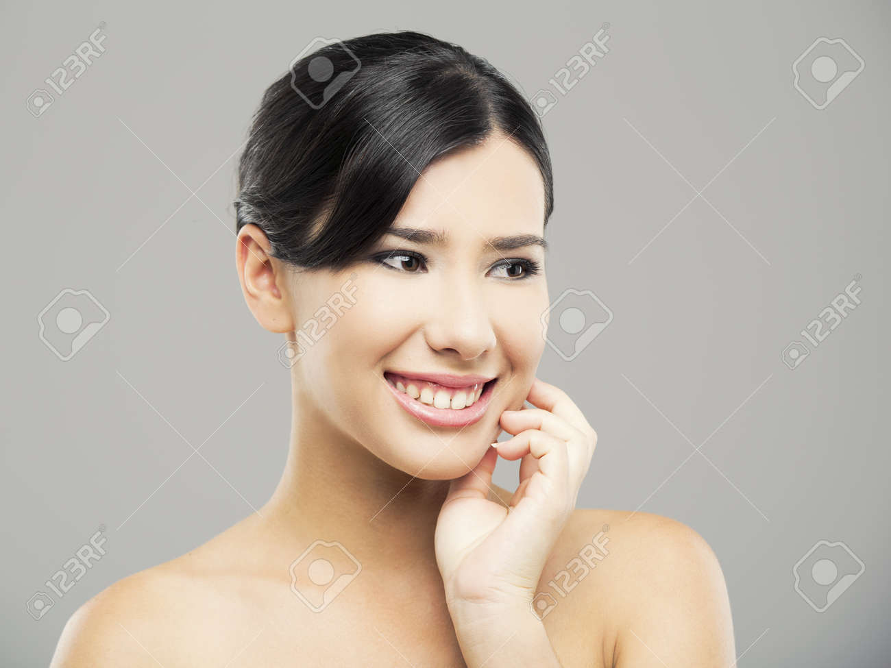 Beauty portrait of young asian woman with a beautiful smile, over a gray background Stock Photo - 18971887