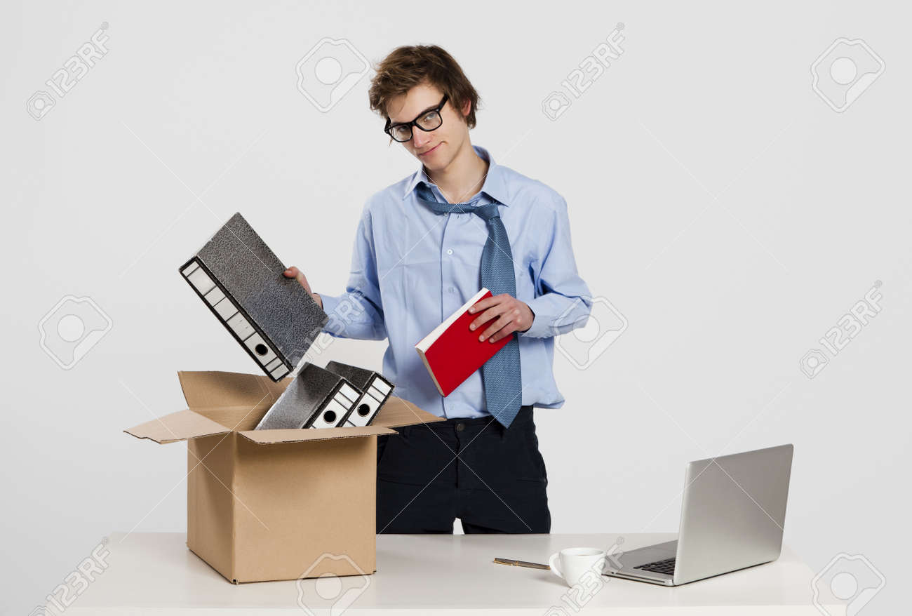 young man in the office packing up after being fired stock photo stock photo young man in the office packing up after being fired