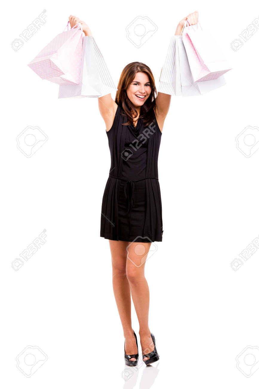 Beautiful and attractive young woman with arms up holding shopping bags, isolated over white background Stock Photo - 24920935