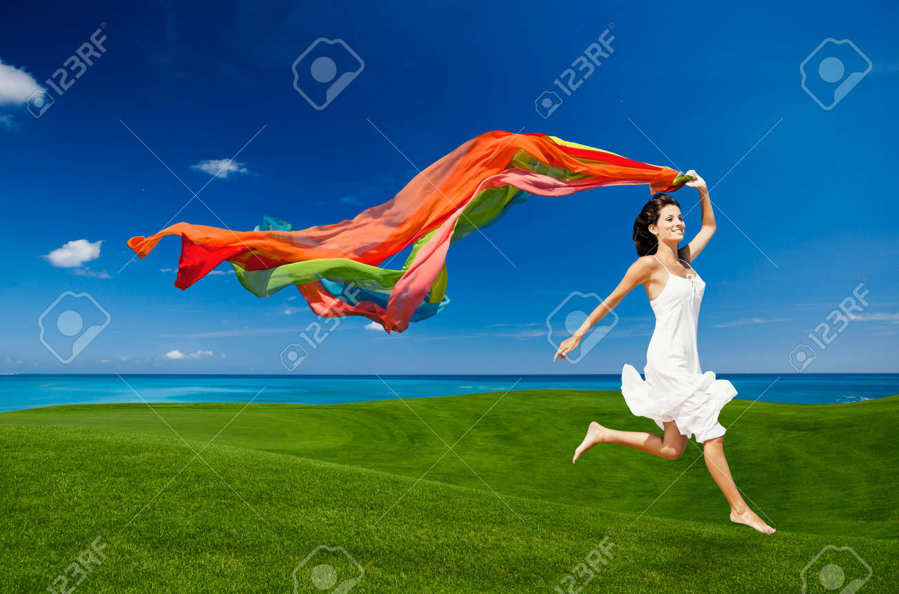 Beautiful woman jumping on a green meadow with colored tissues Stock Photo - 29917402