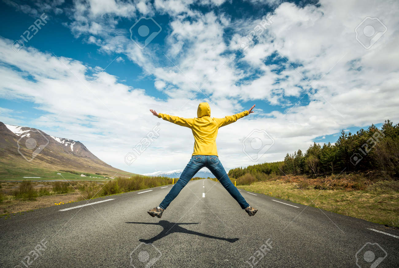 Woman jumping on a beautiful road - 48495351