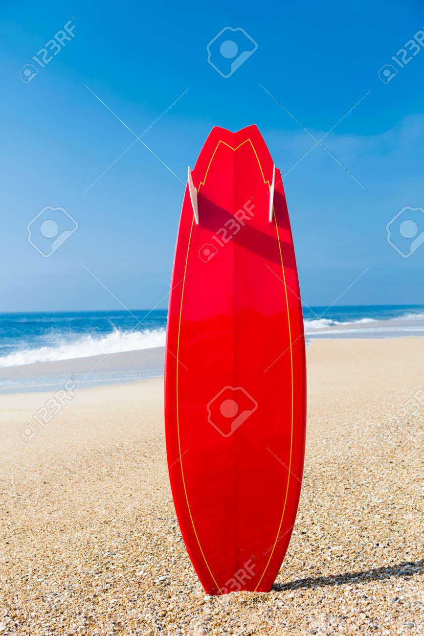 beach landscape with a red surfboard on the sand stock photo