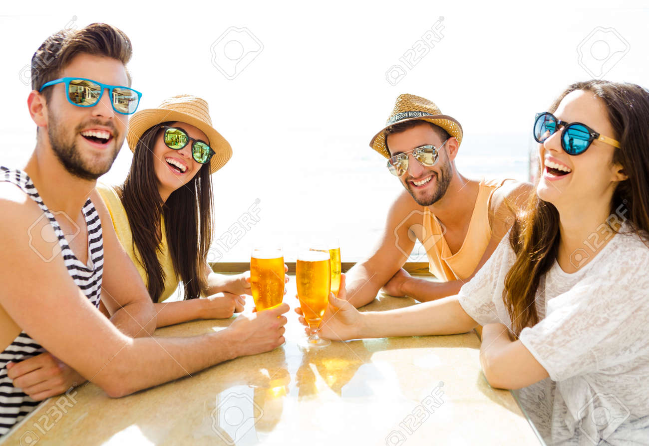 Friends having fun and drinking a cold beer at the beach bar - 51804986
