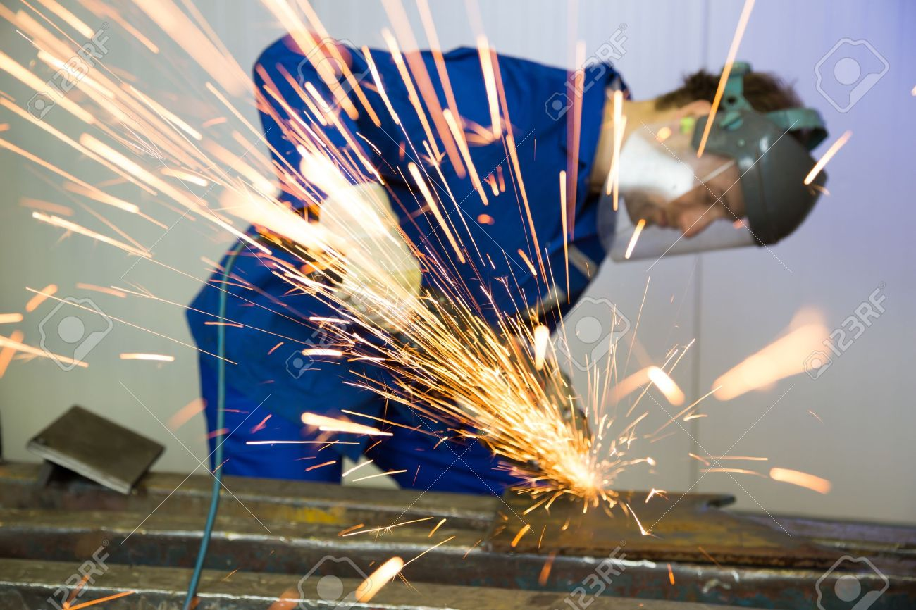 A construction worker using an angle grinder producing a lot of sparks Stock Photo - 17800263