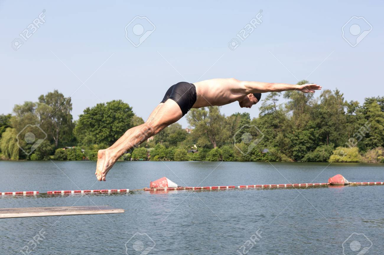 Public Swimming Pools With Diving Boards man jumping off diving board at a public swimming pool stock photo