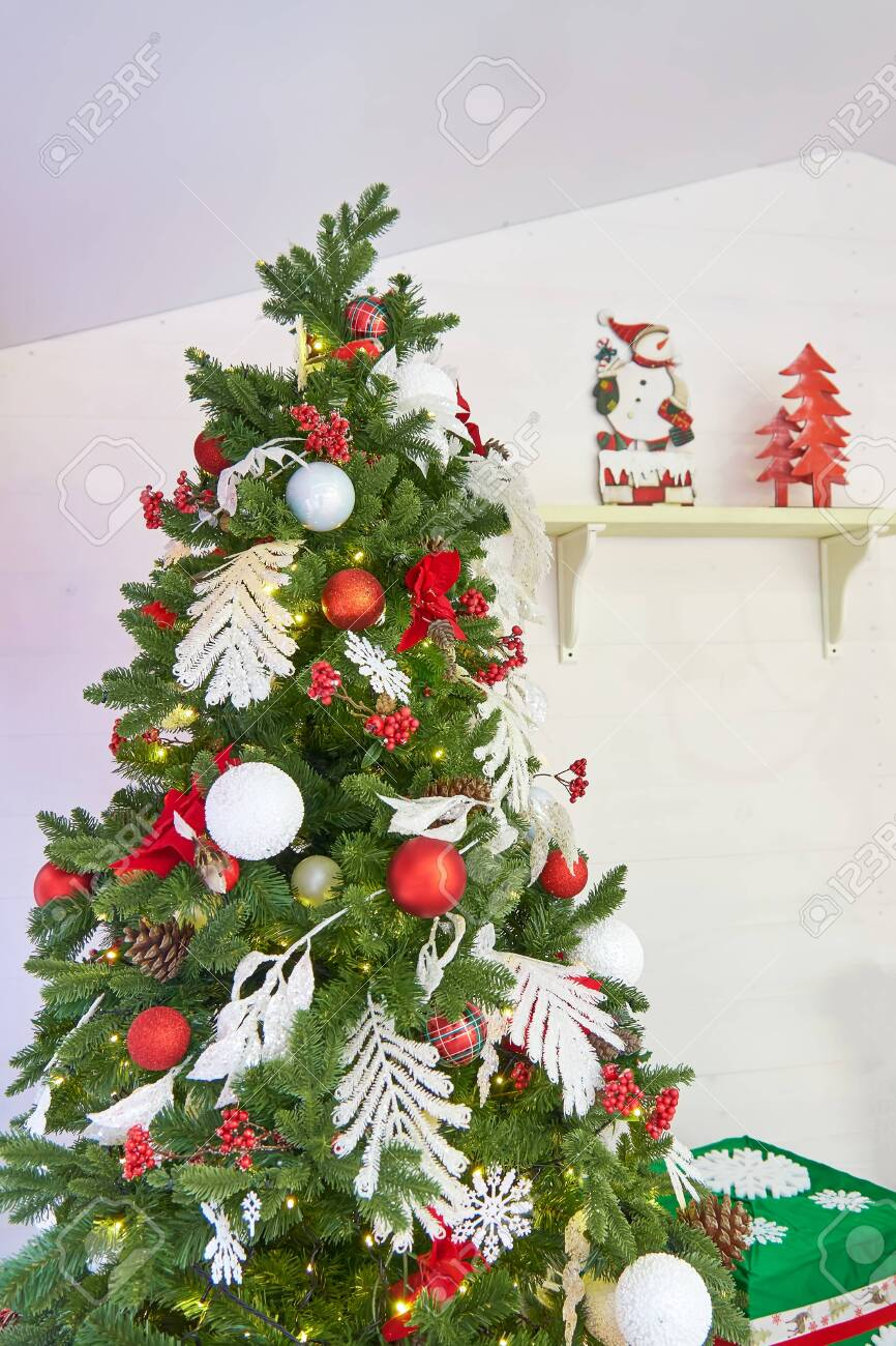 Christmas Tree Decorated With Balls And Bows Near White Wall Stock Photo Picture And Royalty Free Image Image 153398108