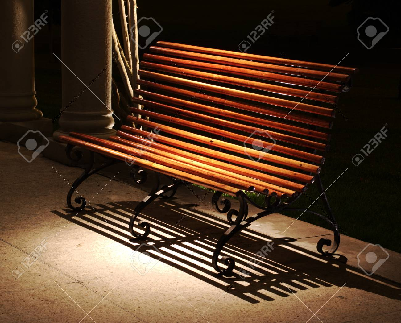 A wooden Bench standing in a Spot Light at Night Stock Photo - 8838340