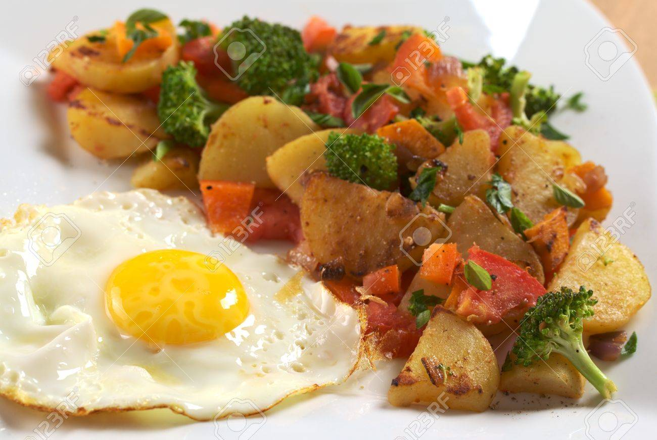 Fried Egg With Fried Potatoes Broccoli Carrot Tomato And Onion And Seasoned With