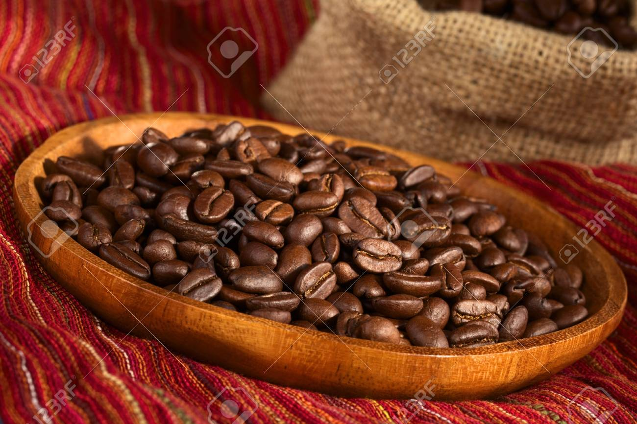 Roasted coffee beans on wooden plate on red cloth with jute bag in the back  Selective Focus, Focus one third into the coffee beans Stock Photo - 13618998
