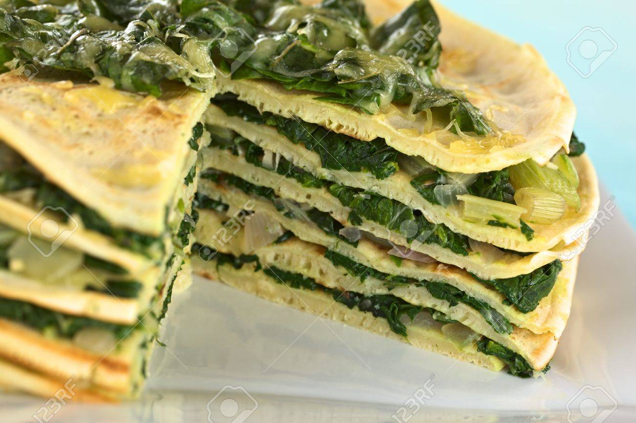 Fresh homemade savory crepes layered with chard (mangold) and onion with cheese on top (Selective Focus, Focus on the right front part of the topping and running down through the cake) Stock Photo - 13765150