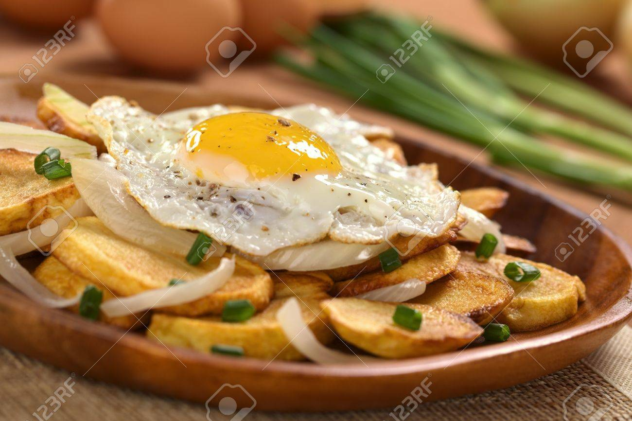 Fresh Homemade Fried Egg On Crispy Fried Potato Slices With Fried Onion And Scallion On Wooden