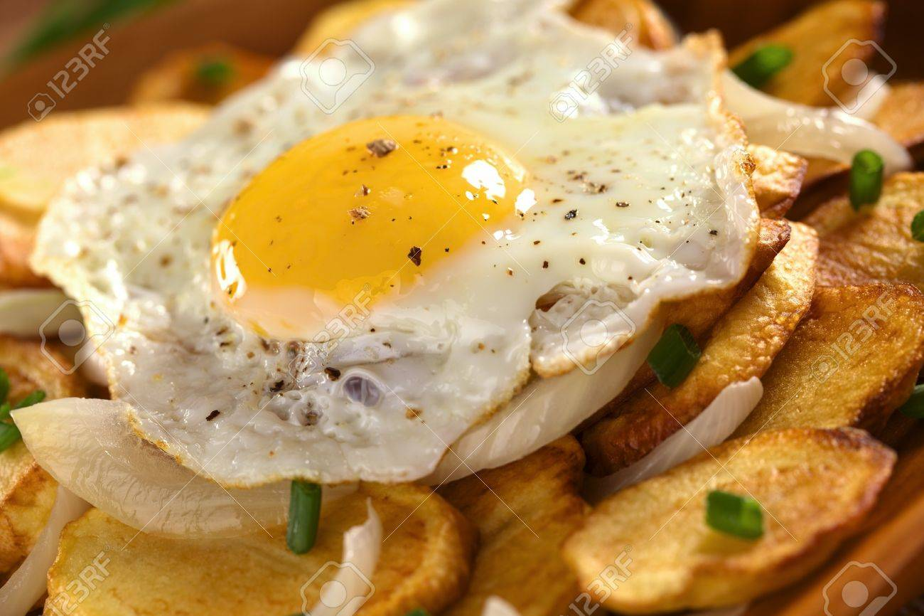 Fresh Homemade Fried Egg With Ground Pepper On Crispy Fried Potato Slices With Fried Onion And