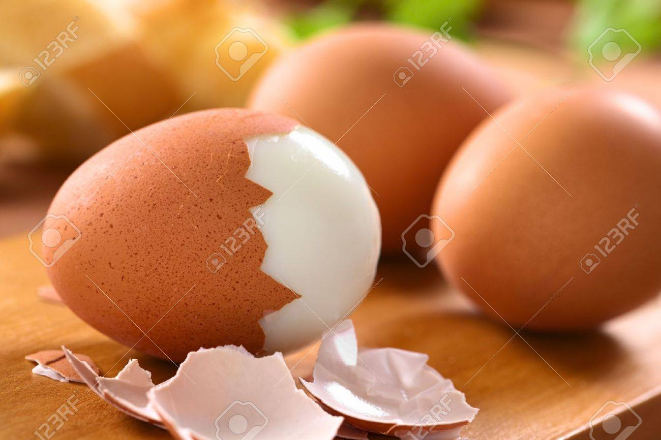 Fresh hard boiled eggs with shell beside on wooden board Selective Focus, Focus on the front of the shell on the first egg - 13911592